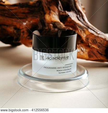 Academie Cream For Skin On Wooden Bark Beige Background With Laboratory Glassware. Face Cream On Ped