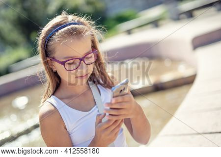 Young Pre-teen Blonde Girl Looks Into The Mobile Phone In Her Hand Sitting On The Edge Of A Fountain