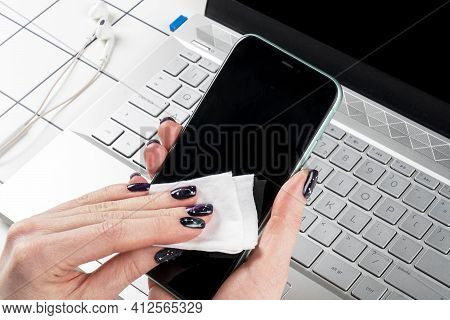 Woman Cleaning Smartphone. Female Hands Disinfecting Mobile Phone With Antivirus Wet Wipes. Cleaning