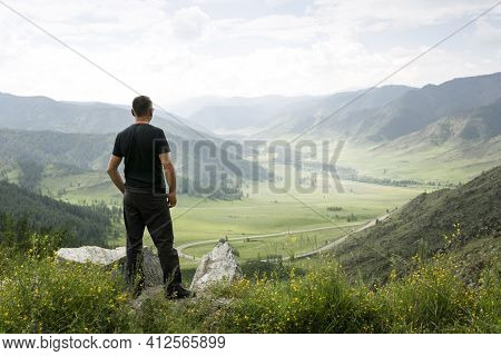 Adult Man Standing On Top Of Cliff In Summer Mountains And Enjoying View Of Valley. Wanderlust Adven