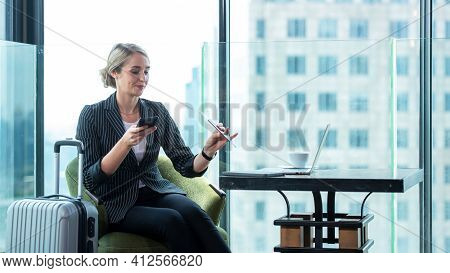 Business Woman Holding Passport And  Using Smartphone Check In Air Ticket  And Boarding Card In Depa