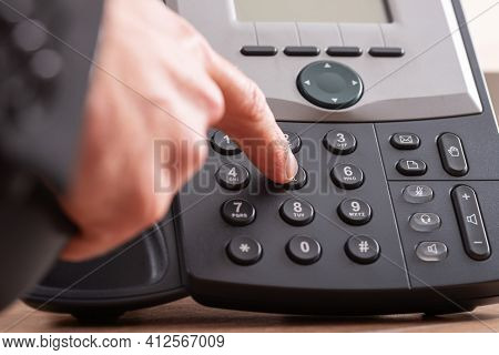 Closeup View Of Male Finger Dialing Telephone Number On Black Landline Phone.