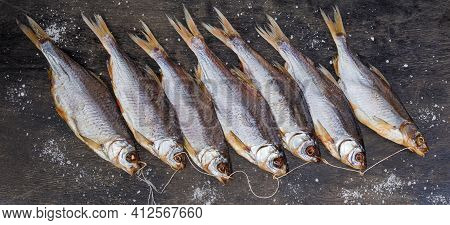 Bunch Of Salted And Air-dried Roach Fish On A Black Surface Sprinkled With Coarse Salt, Top View