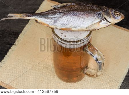 Salted And Air-dried Roach Fish Lies On A Beer Glass With Lager Beer On A Napkin On A Dark Table, To
