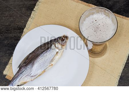 Beer Glass With Lager Beer Against A Salted And Air-dried Roach Fish On Dish On A Napkin On A Dark T