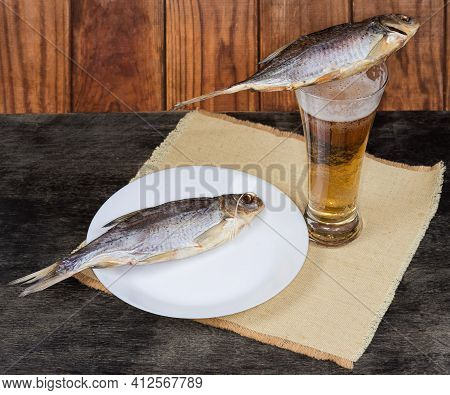 Two Salted And Air-dried Roach Fish Lie On A Beer Glass With Lager Beer And On Dish On A Napkin On A