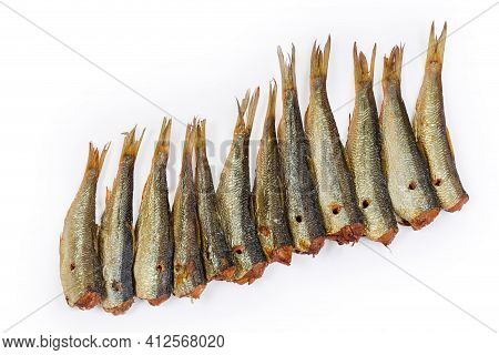 Smoked Headless Sprats Laid Out In A Row On A White Background, Top View