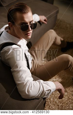 Men's fashion. Well-groomed young man in elegant clothes and sunglasses sits by a leather sofa in a modern luxurious apartment. Business style, businessman.