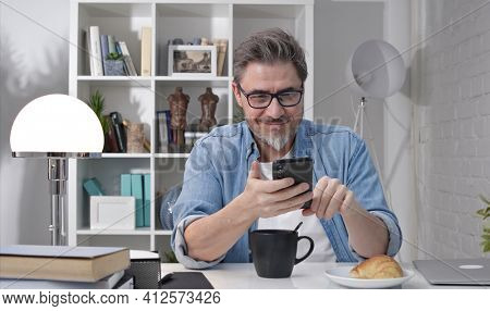 50s man having breakfast checking news on phone drinking morning coffee at home. Confident happy smiling.