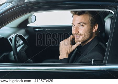 Happy young car driver traveling driving luxury car, smiling. Limousine service, chauffeur.