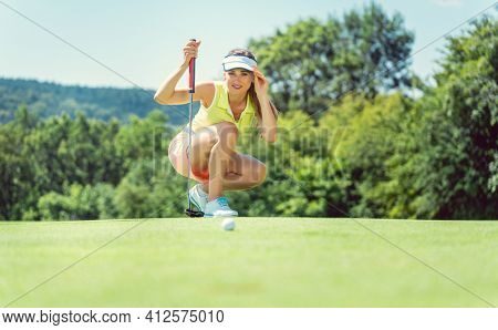 Woman on golf course taking measure on the green