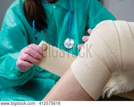 A Nurse Wearing Medical Gloves And A Mask Wraps An Elastic Bandage Around The Patients Leg And Knee.