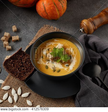 Pumpkin cream soup with pumpkin seeds and dried bread cubes. Lenten menu. Healthy, vegetarian food. Bowl with soup  and orange pumpkins on gray background. Square format.