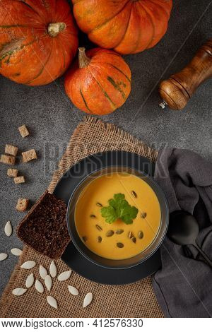 Pumpkin cream soup with pumpkin seeds and dried bread cubes. Lenten menu. Healthy, vegetarian food. Bowl with soup  and orange pumpkins on gray background. Top view.