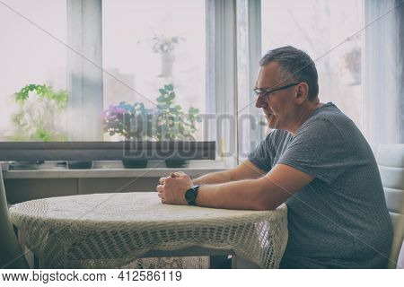 Single man suffers from loneliness or depression. The man is sitting in the living room at the table