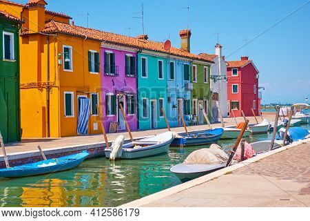 Canal with moored motorboats and colorful houses in Burano in Venice, Italy. Venetian cityscape