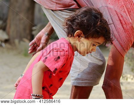 An Indian-origin Little Boy With Grandfather Looking Towards The Ground, India.concept For Childhood