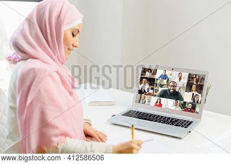 Arab Woman In Hijab Having A Video Chat On Laptop, Speaking To The Web Camera, Sitting At The Desk,