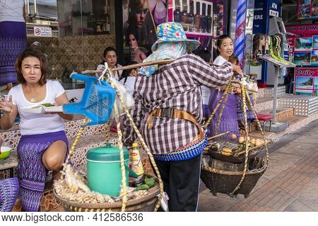 Thai Women Masseuses Have Lunch Right On The Street, Sitting At The Massage Parlor On Bangla Road. A