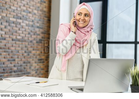 Business Muslim Woman In Hijab At Office, Standing At The Desk With Laptop, Talking By Mobile Phone,