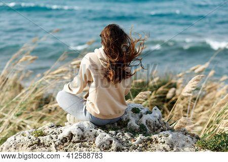 Young Yoga Woman Meditation, Mindfulness On Seaside Rock Cliff Edge. Beautiful Sea View. Windy Wheat