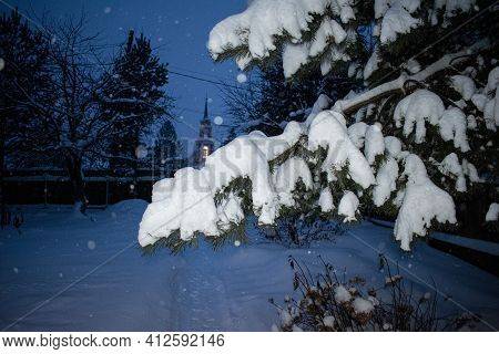 Snowy Spruce Or Fir-tree Branch At Night Winter. The Courtyard Of A Private House.