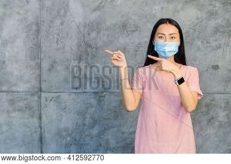 Pretty Woman With Medical Mask And Smart Watch On The Hand, Standing Against Gray Wall, Pointing To