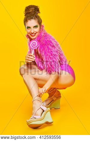Stunning fashionable model posing in colorful clothes with lollipop on a vivid a yellow background. Active bright lifestyle. Copy space.