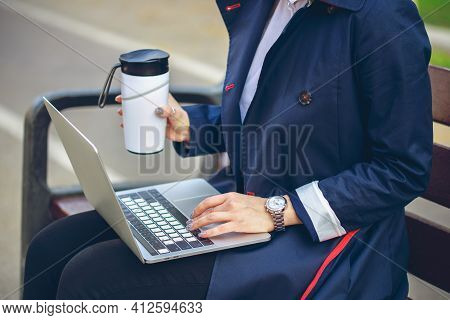 Unrecognaseble Businesswoman Working On Bench With Laptop And Takeaway Reusable Coffee Cup. Freelanc
