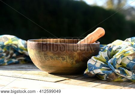 Tibetan Singing Bowl With Scarf On A Table. Translation Of Mantra Transform Your Impure Body, Speech