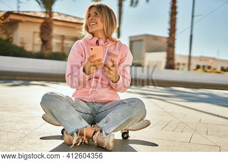Young blonde skater girl using smartphone and drinking coffee sitting on the skate