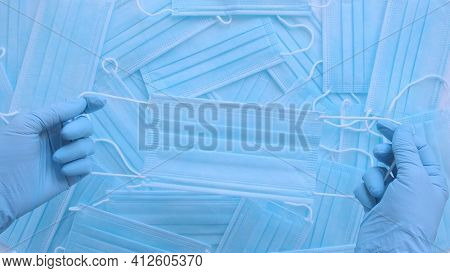 Medical Masks. Doctor Holds Respiratory Surgical Face Mask In Hands Blue Medical Gloves On Blue Back