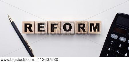 On A Light Background Between The Calculator And The Pen There Are Wooden Cubes With The Word Reform