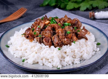 Stewed Chicken Gizzards On The Boiled Rice. Hot Meal With Offal Meat Products