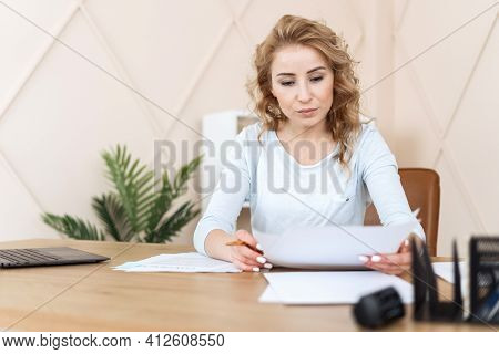 Focused Woman Sitting In Office Behind Desk, Checking Report Or Agreement, Signing Legal Document Fo