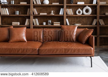 Comfortable Sofa Standing In Library Against Collections Books On Bookshelves. Brown Leather Couch S