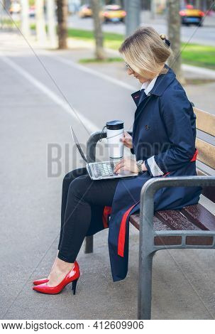Young Woman In A Business Suit And Autumn Coat Working Using Laptop On Bench, Drinking Takeaway Coff