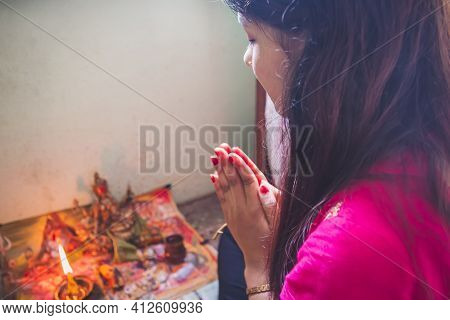 Hindu Woman Offering Paryers To God At Home. Hindu Devotee Praying With God By Doing Namaste. Nepali