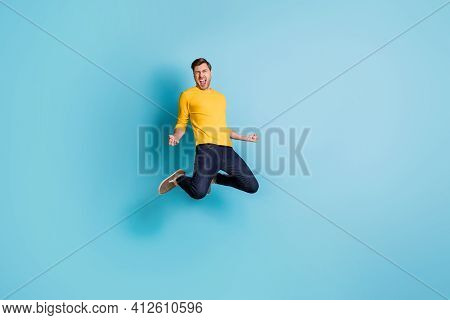 Full Length Photo Of Crazy Happy Man Winner Jump Up Air Hold Fists Scream Isolated On Pastel Blue Co