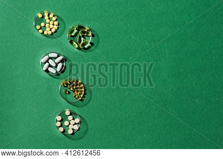 Vitamins Capsules On Green Background, Top View, Copy Space. Food Supplements: Fish Oil, Omega 3, Om
