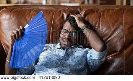 Overheated Afro American Man Recline On Couch Use Hand Fan