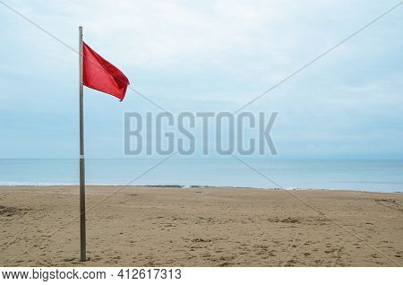 Empty Sandy Beach And Red Storm Flag On A Cloudy Day. Security On Public And Private Beaches, Storm