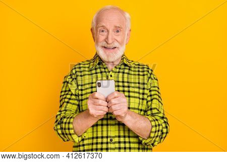 Photo Of Cheerful Aged Man Pensioner Browse Cellphone Chat Type Sms Feel Young Isolated Over Yellow