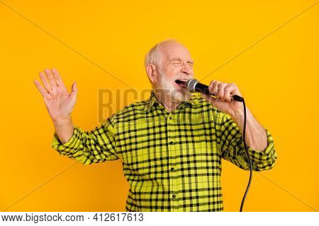 Photo Of Aged Man Excited Enjoy Sing Song Microphone Karaoke Event Isolated Over Yellow Color Backgr