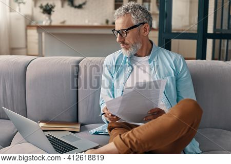 Busy Senior Man Checking The Papers And Using Laptop While Sitting On The Sofa At Home