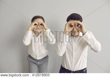 Cheerful Father And Little Son Look Into Imaginary Binoculars Made Of Their Hands.
