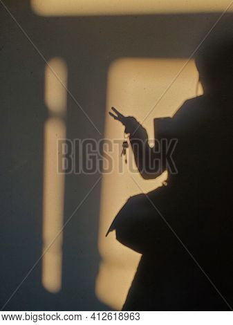 Blurred Shadows Of Woman Hand Holding Bunch Of Keys. Female Silhouette Of Shadow On Brown Wall Backg