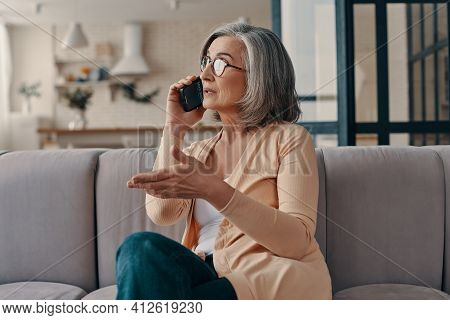 Beautiful Senior Woman In Casual Clothing Talking On The Smart Phone While Sitting On The Sofa At Ho