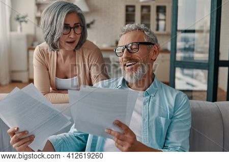 Modern Senior Couple In Casual Clothing Taking Care Of Their Taxes While Bonding Together At Home