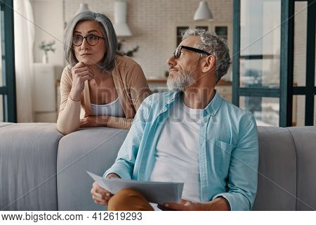 Thoughtful Senior Couple In Casual Clothing Taking Care Of Their Finances While Bonding Together At